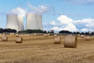 A nuclear power plant behind a field.