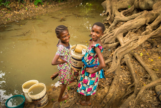 Girls collect water in buckets.